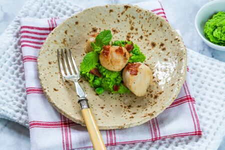Scallops with minted peas and crispy pancetta Stock Photo