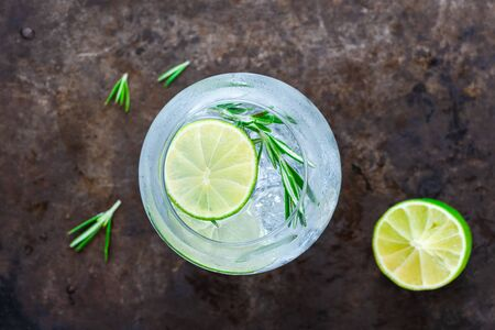Gin and tonic cocktail with lime and rosemary - refreshing summer alkoholic drink - overhead view Stock Photo