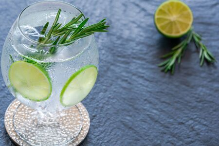Gin and tonic cocktail with lime and rosemary - refreshing summer alkoholic drink 免版税图像