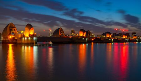LONDON, UK - JUNE 29, 2019: Night view of Canary Wharf, one of the main financial centres of the UK across River Thames, and Thames Barrier, the worlds second largest movable flood barrier