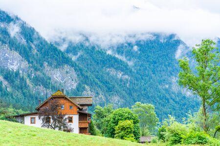 Landscape with traditional house in Salzkammergut, an Austrian region of lakes and Alpine ranges near Salzburg, Austria