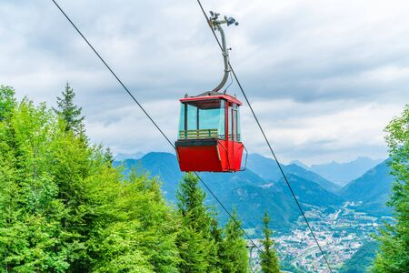 Red vintage gondola of Mount Katrin cable car and panoramic alpine view of peaks over Bad Ischl, Salzkammergut, Austria
