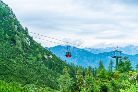 Colorful vintage gondola of Mount Katrin cable car and panoramic alpine view of peaks over Bad Ischl, Salzkammergut, Austria
