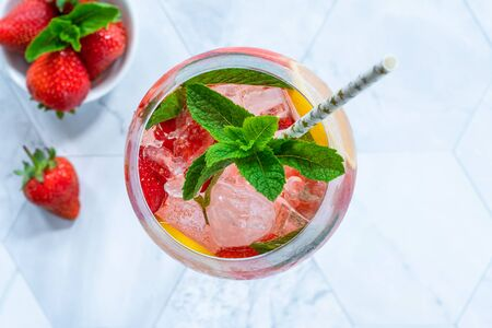 Pink gin and tonic cocktail with prosecco and strawberries, garnished with fresh mint - refreshing summer alcoholic drink Stock Photo - 128573536