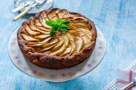 Apple, ginger and honey cake garnished with fresh mint Stock Photo - 128573463