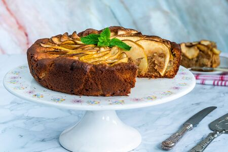 Apple, ginger and honey cake garnished with fresh mint Stock Photo - 128573472