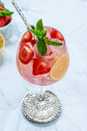 Pink gin and tonic cocktail with prosecco and strawberries, garnished with fresh mint - refreshing summer alcoholic drink