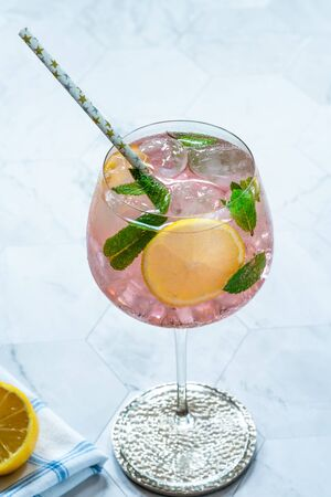 Pink gin and tonic cocktail with lemon slices, garnished with fresh mint leaves - refreshing summer alcoholic drink