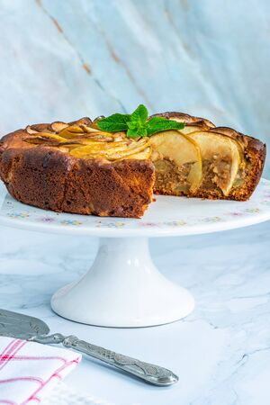 Apple, ginger and honey cake garnished with fresh mint Stock Photo - 128573450
