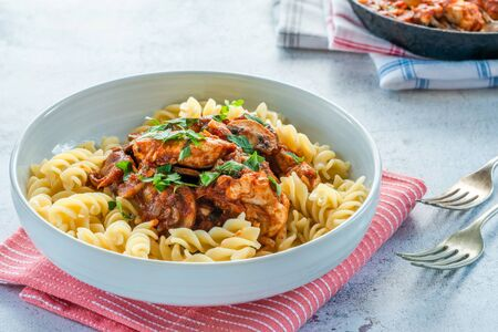 Smoky chicken and mushrooms with tomto sauce and pasta in a bowl