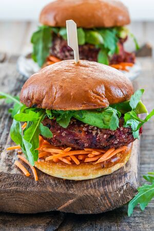 Vegetarian beetroot burger with avocado and carrot slaw in brioche bun