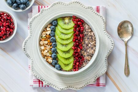 Summer porridge with mixed seeds and fresh fruit - blueberries, pomegranate and kiwi. Healthy breakfast.