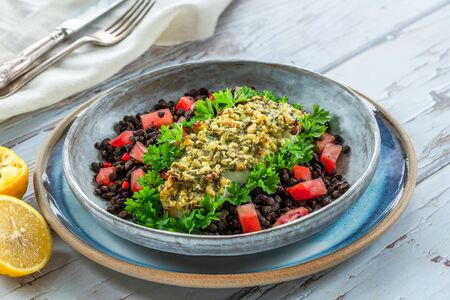 Pesto-crusted cod with Puy lentils and tomatoes in a bowl Stock Photo