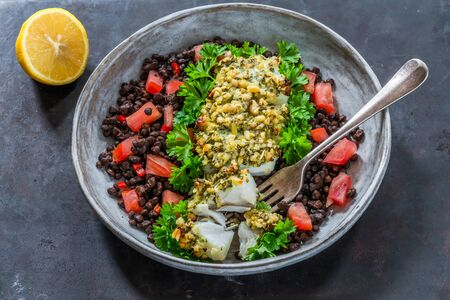 Pesto-crusted cod with Puy lentils and tomatoes - high angle view
