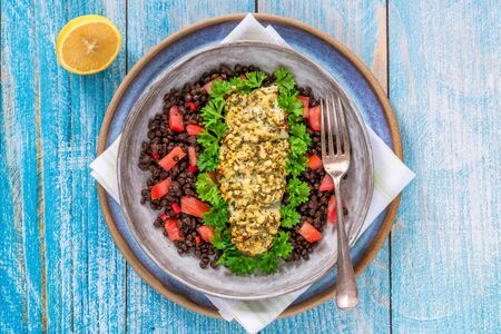 Pesto-crusted cod with Puy lentils and tomatoes - overhead view Stock Photo