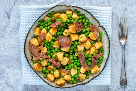 Potato gnocchi with green peas, pesto, proscuitto and chorizo in a bowl - overhead view