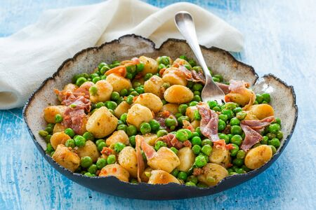 Potato gnocchi with green peas, pesto, proscuitto and chorizo in a bowl Stock Photo
