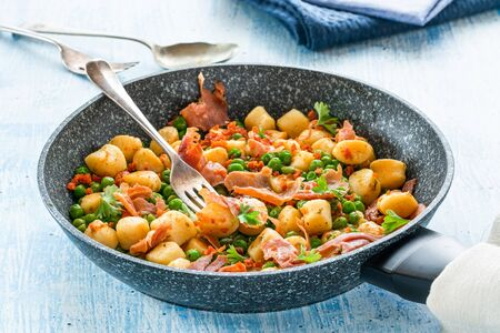 Potato gnocchi with green peas, pesto, proscuitto and chorizo in frying pan Stock Photo