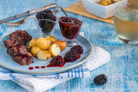 Pan-fried venison with blackberry sauce and boiled baby potatoes