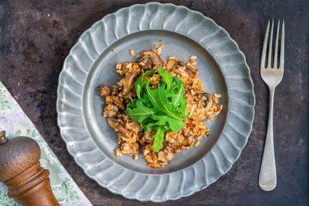 Mushroom, chorizo and thyme risotto with rocket lettuce - overhead view