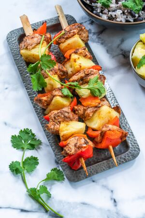 Jerk-style chicken and pineapple skewers with black bean rice - high angle view