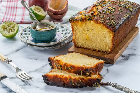 Lime and passion fruit drizzle cake on wooden board Фото со стока - 134262699