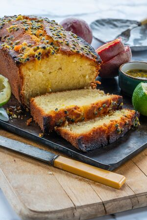 Lime and passion fruit drizzle cake on wooden board