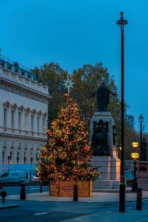 LONDON - NOVEMBER 21, 2019: Christmas tree at Waterloo Place opposite the Sofitel Hotel St James's is decorated in gold and bronze colour scheme. 写真素材 - 136347147
