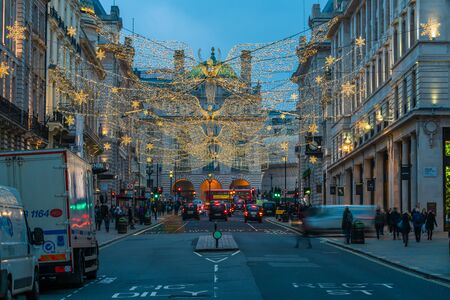 LONDON - NOVEMBER 21, 2019: Christmas lights on Regents Street St James. Beautiful Christmas decorations attract thousands of shoppers during the festive season and are a major tourist attraction. 写真素材 - 136347151