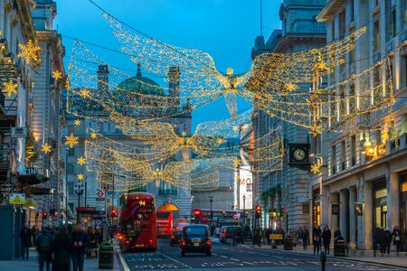 LONDON - NOVEMBER 21, 2019: Christmas lights on Regents Street St James. Beautiful Christmas decorations attract thousands of shoppers during the festive season and are a major tourist attraction. 写真素材 - 136347153