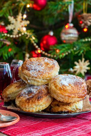 Homemade Christmas puff pastry mince pies with Christmas tree in the background