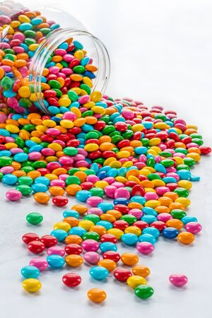 Colorful candy spilling out of a jar onto white