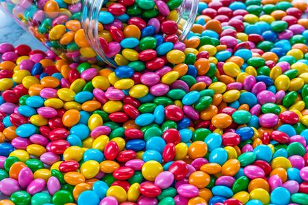 Colorful candy spilling out of a jar