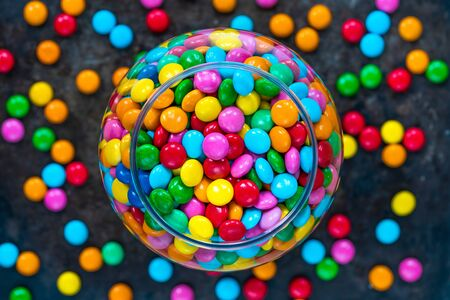 Colorful candy sweets in a jar on dark Фото со стока
