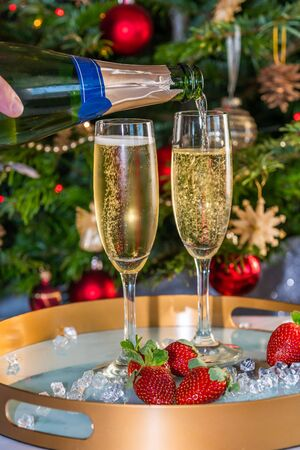Champagne poured into glasses with strawberries on festive 写真素材 - 136792721