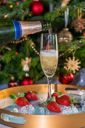Champagne poured into glass with strawberries on festive background 写真素材 - 136550506