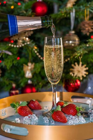 Champagne poured into glass with strawberries on festive background Фото со стока