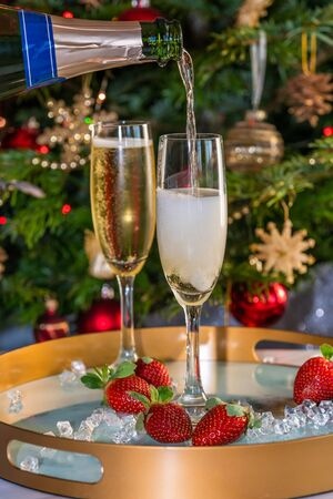 Champagne poured into glasses with strawberries on festive Фото со стока