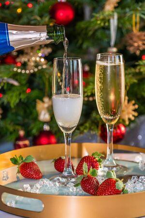 Champagne poured into glasses with strawberries on festive 版權商用圖片