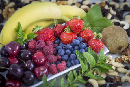 Berries, cheriies, bananas and nuts and raisins. photo