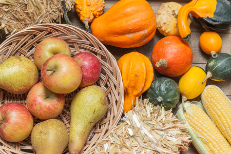 harvest cone cornucopia: Pumpkins, apples, pears, tomatoes and straw on a wooden basket.