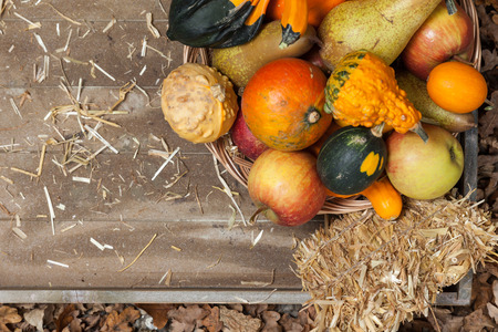 harvest cone cornucopia: Pumpkins, apples, pears, tomatos and straw on a wooden plate.