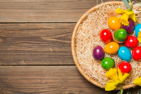 Easter nest with colorful eggs and yellow daffodils on a wooden table. photo