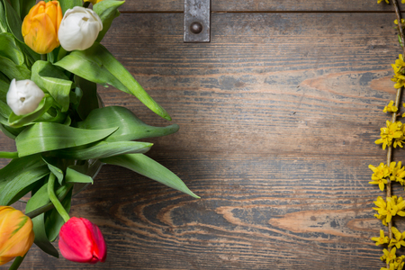 Tulips in an vase and flowers on a wooden chest photo