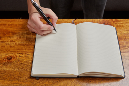 scheduler: Woman writing in a book with a fountain pen