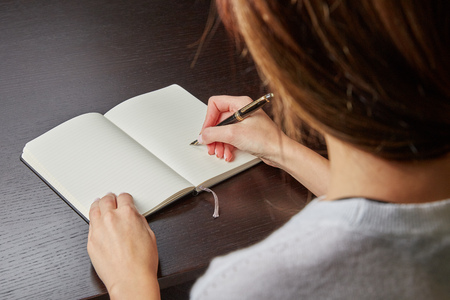 person writing: Woman writing in a book with a fountain pen