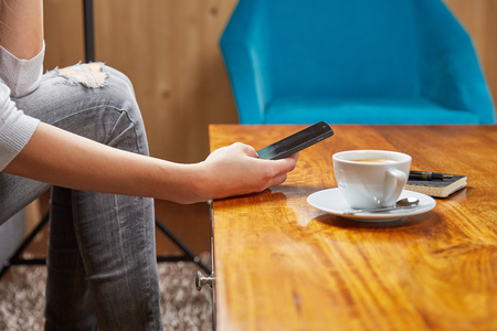 scrolling: Woman with mobile phone, coffee and notepad  in cafe Stock Photo