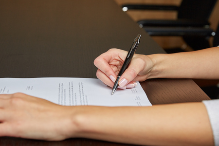writing paper: Woman writing on a white sheet of paper, signing a contract