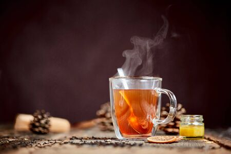 Hot black tea with steam and honey on a wooden table Stock Photo