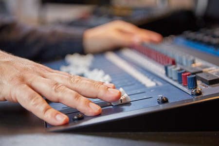 radio dj: Perspective view of a mixing desk where the audio engineer is working.